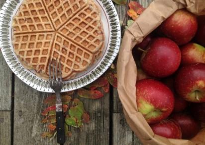 Äppelvåfflor på en tallrik och en pappåse bredvid fylld med äpplen