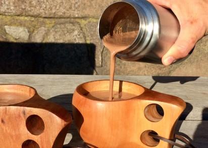 Häller upp varm choklad från en termos i träkåsor