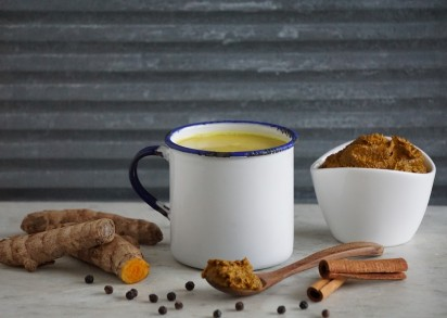 En mugg med guldmjölk och bredvid ligger gurkmeja, kanel och svartpepparkon samt en liten skål med gurkmejapasta