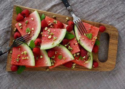 Vattenmelon, hallon, pistagenötter och mynta på en skärbräda