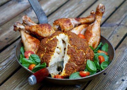 Helrostad blomkål i en stekpanna tillsammans med grillade kycklingben och sallad