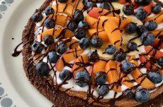 Ljuvlig Efterrättspizza med en choklad brownie botten toppad med mandelsmör, fräsch kokosyoghurt, frukt och bär.