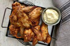 Ugnsstekta kycklingvingar på plåt, serverade med en vitlök och chilimajonnäs.