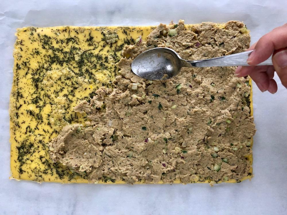 Tonfiskröra beds över omeletten med en sked