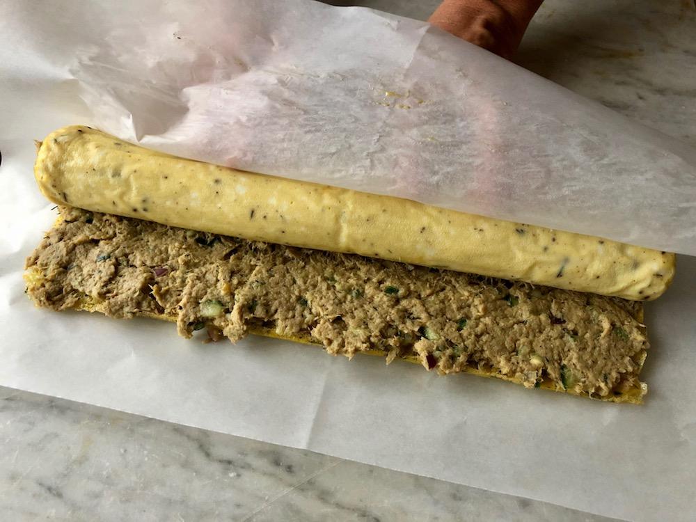 Rullar ihop tonfiskrullen med hjälp av bakplåtspappret