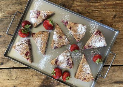 Jordgubbsscones på plåt tillsammans med färska jordgubbar