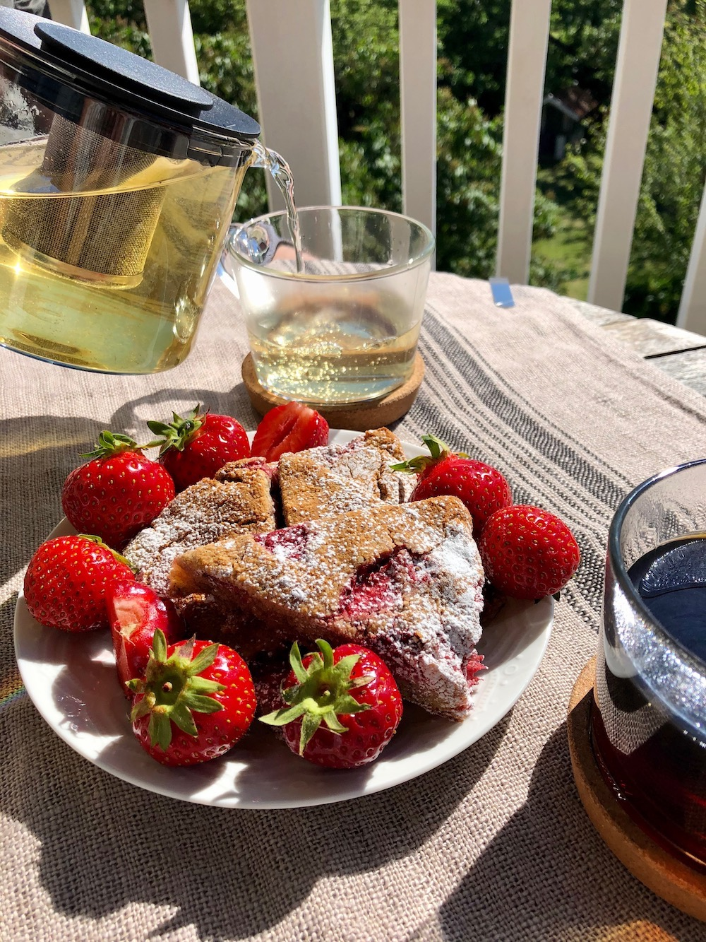 Jordgubbsscones redo att avnjutas tillsammans med kaffe och te i solskenet