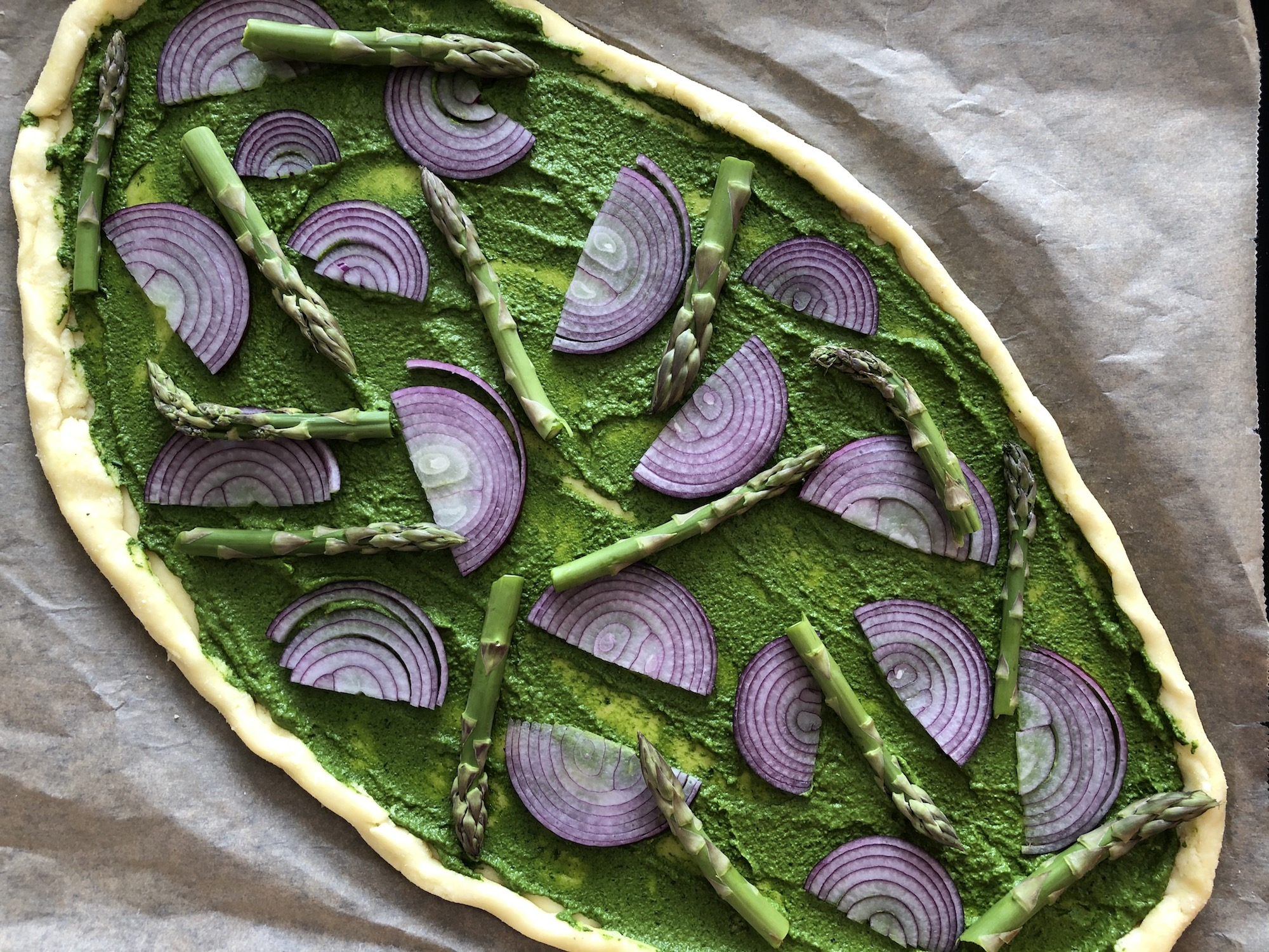 grön pizza toppad med rödlök och sparris redo för ugnen