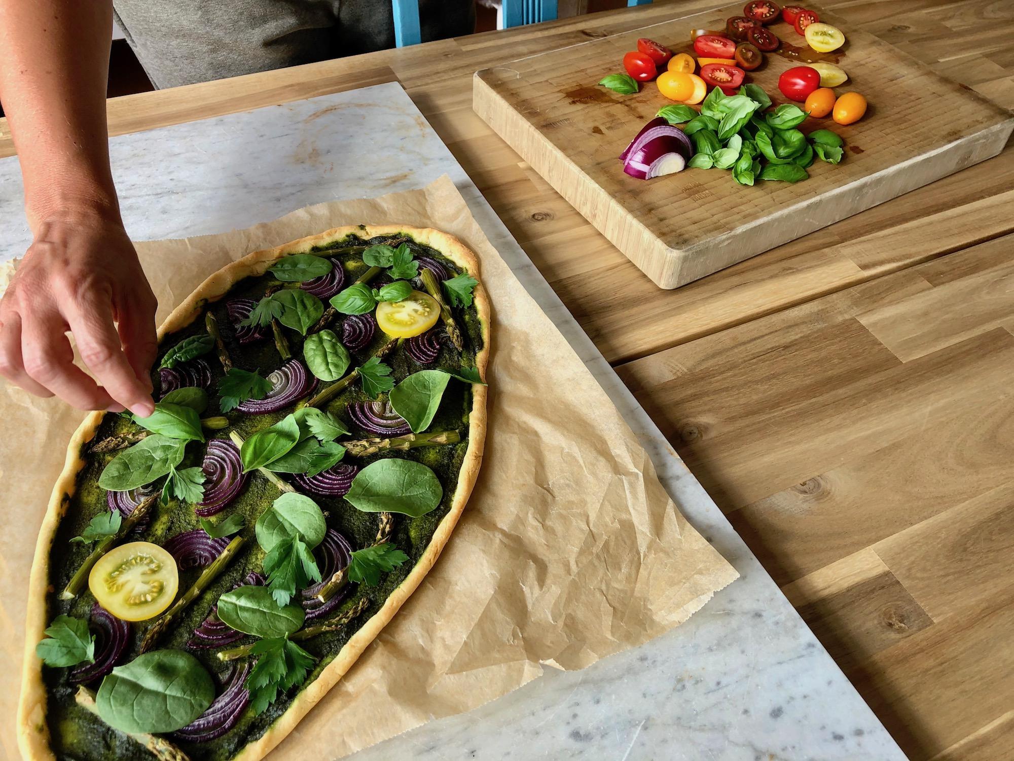 Toppar den gröna pizzan med babyspenat, örter och tomat
