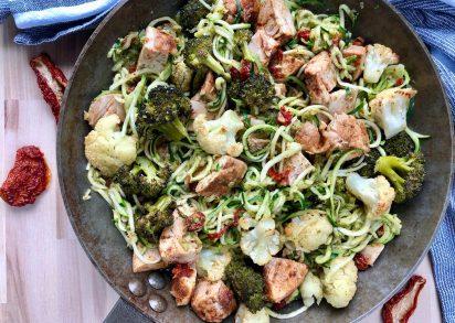 Zucchinipasta med kyckling, pesto och soltorkade tomater redo att avnjutas direkt från pannan