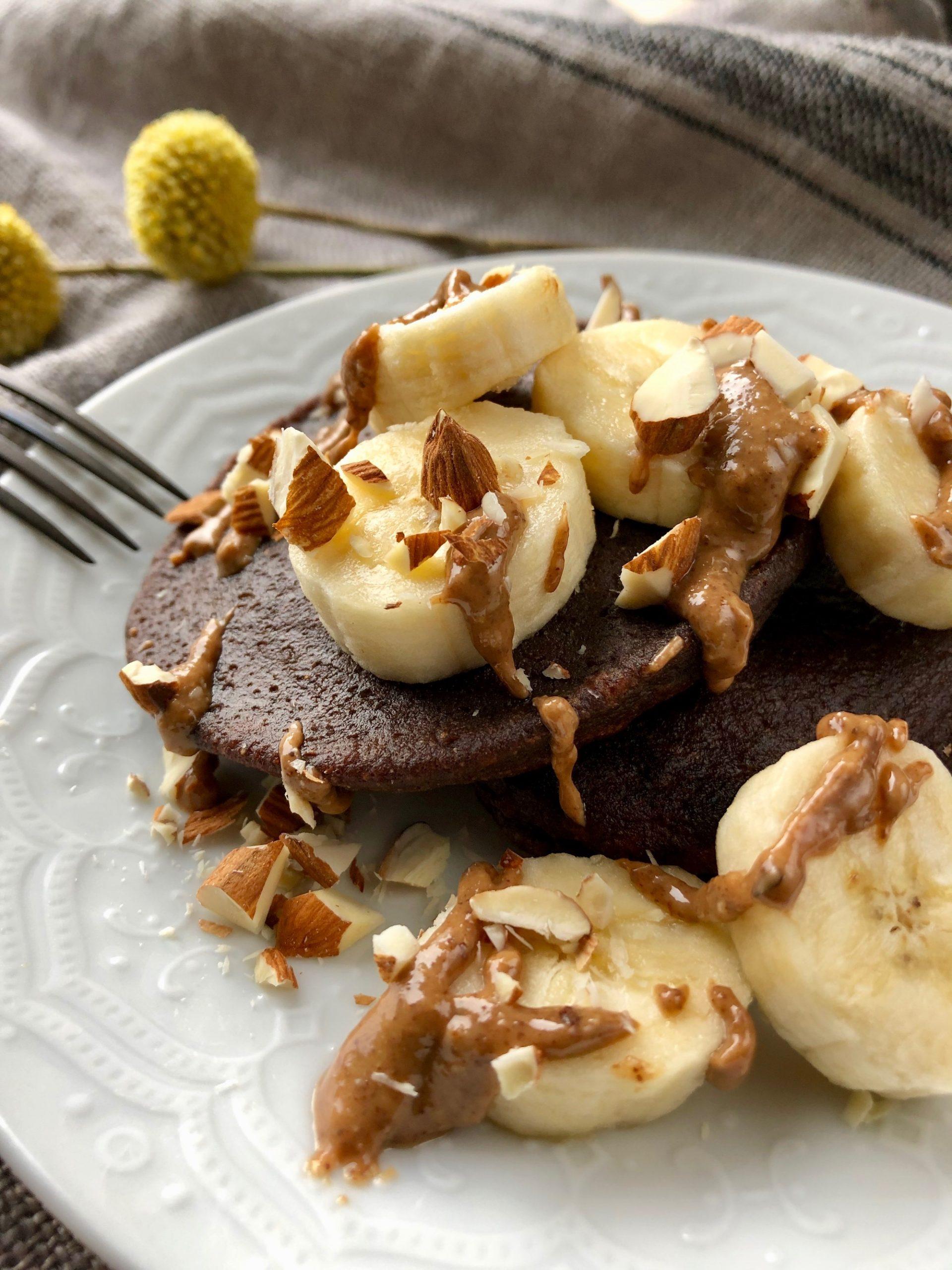 Äggfria chokladplättar på bananmjöl toppade med banan, mandelsmör och hackad mandel