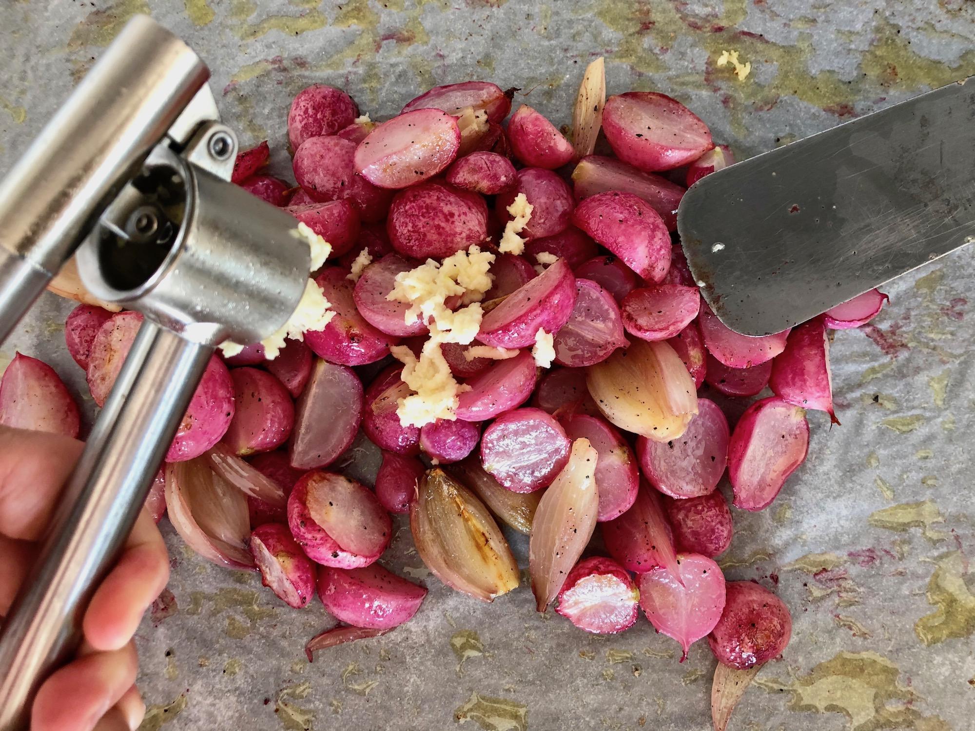 Vitlök som pressas över rostade rädisor